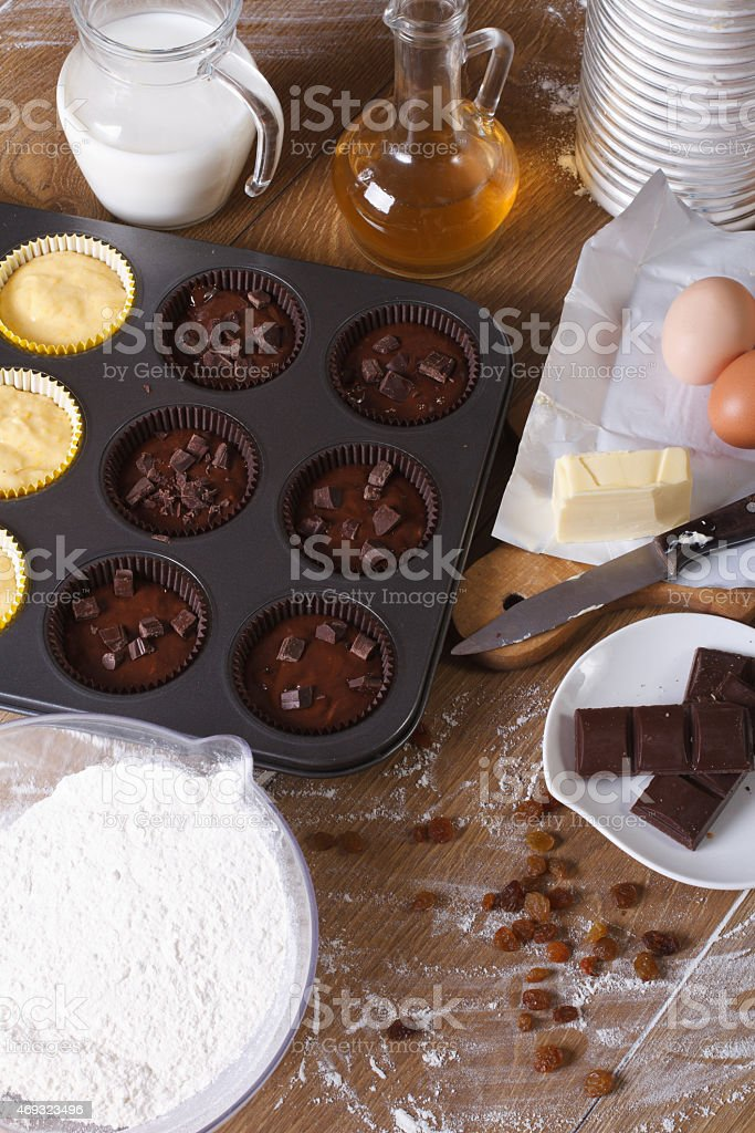 cooking chocolate and vanilla cupcakes close-up vertical stock photo