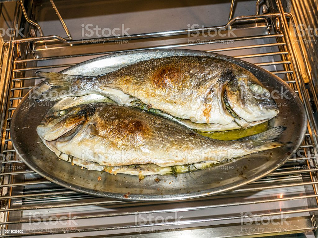 cooking fish in oven at home kitchen stock photo