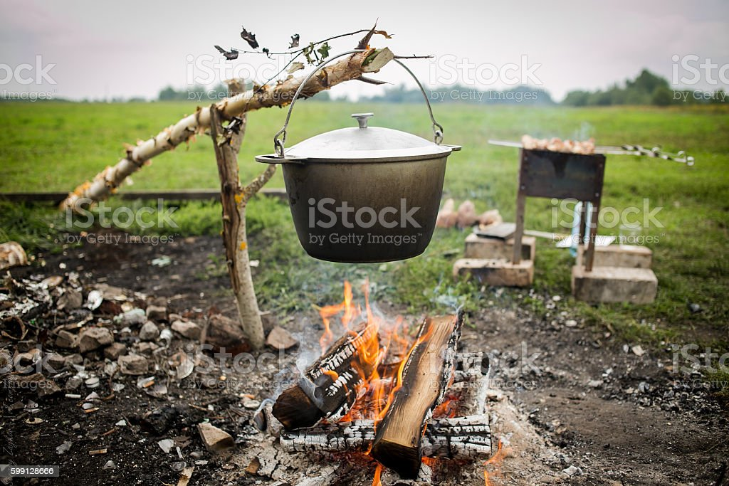 cooking fish soup in pot on bonfire. stock photo