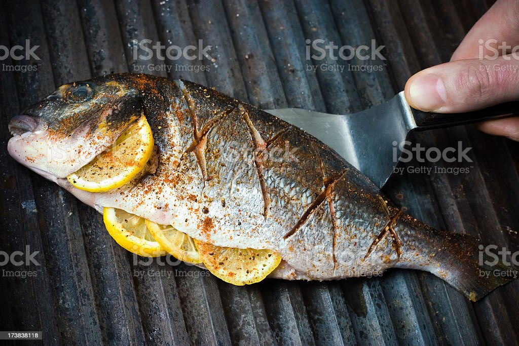 Cooking fish with spices and lemon royalty-free stock photo