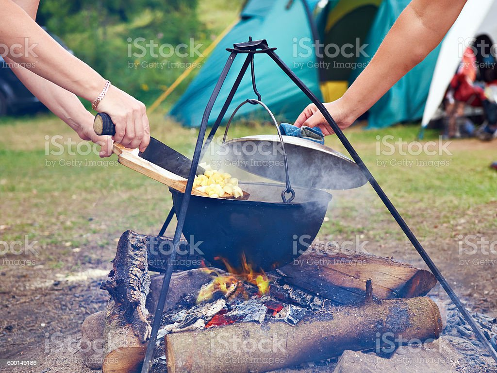 Cooking food over campfire in hike stock photo