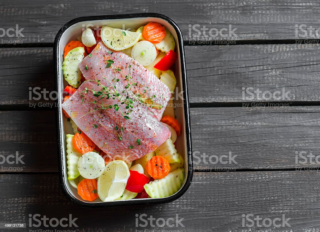 Cooking healthy food - baked fish with vegetables stock photo