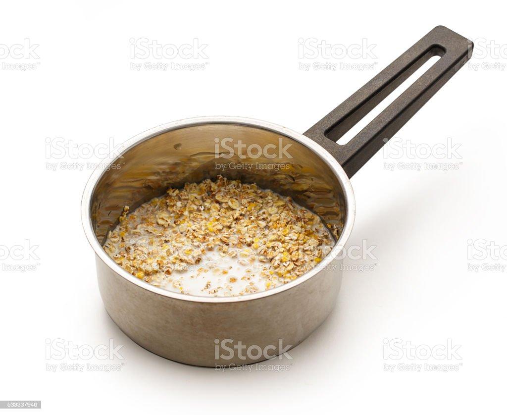 Cooking healthy porridge in metal pot stock photo