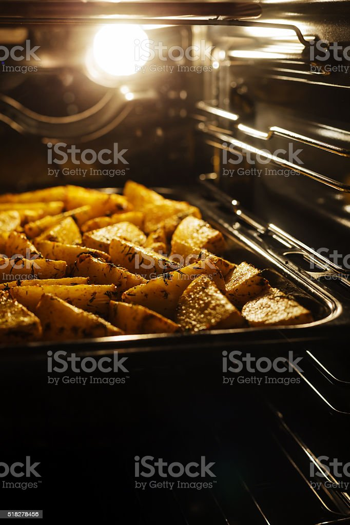 Cooking hot potato in the oven at home stock photo