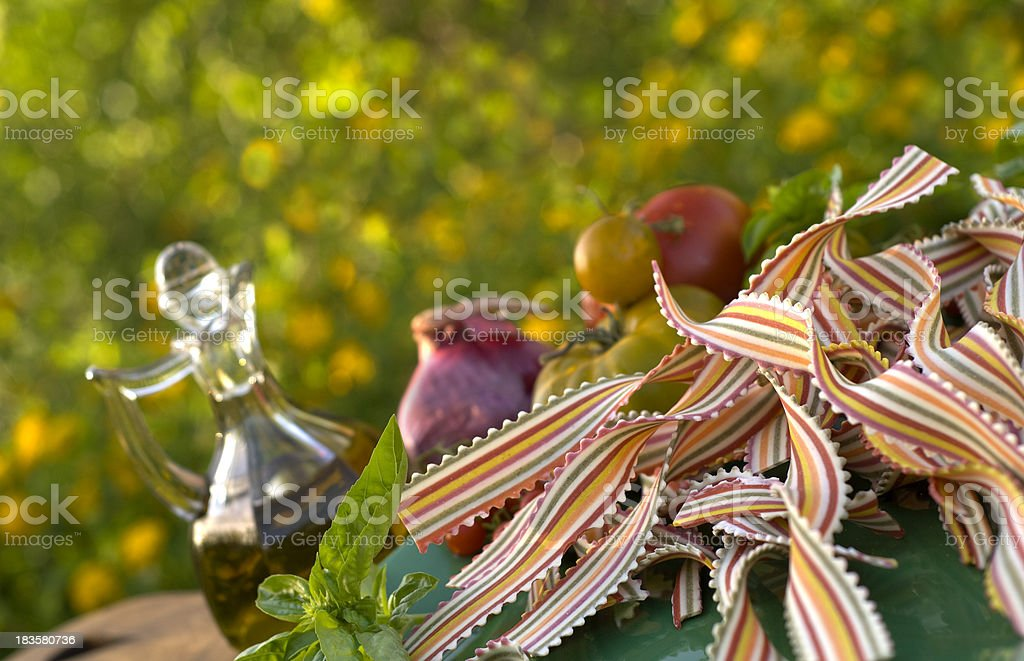 Cooking Italian Pasta Dinner Ingredients: Heirloom Tomatoes, Olive Oil & Basil royalty-free stock photo