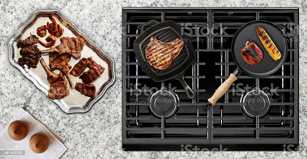 Cooking juicy meat on gas stove stock photo