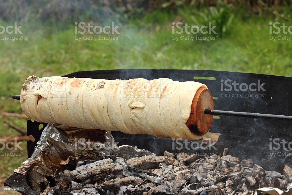 cooking kurtos kalacs on camp fire stock photo