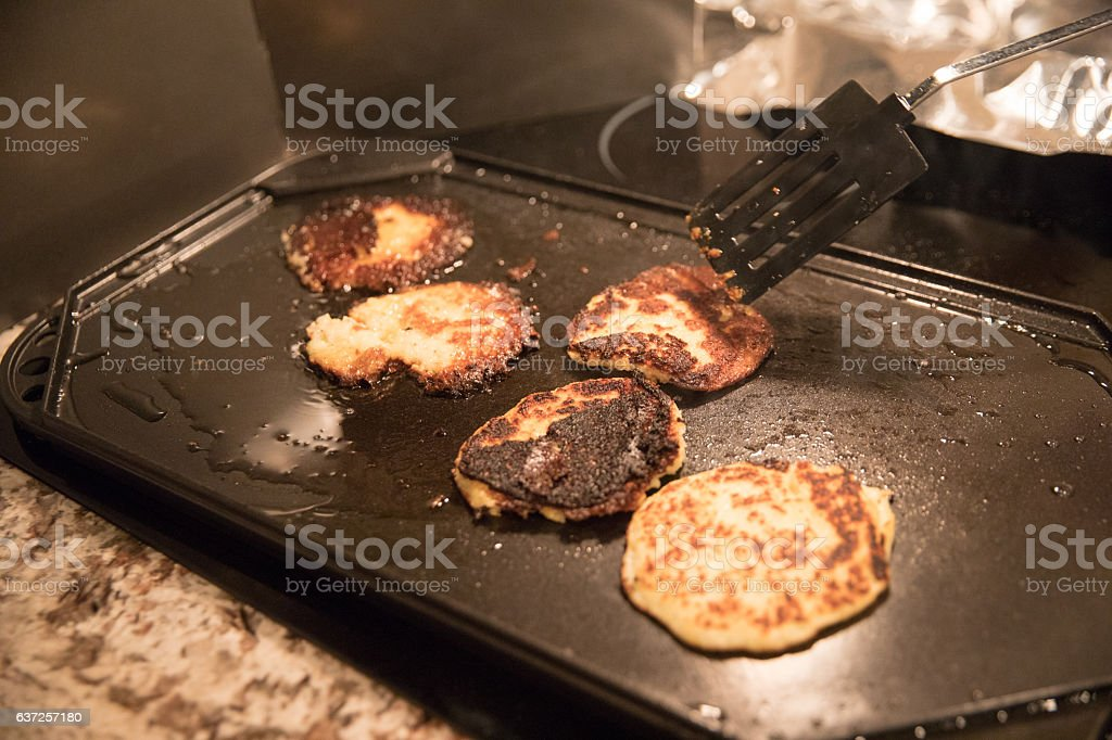 Cooking mishap. Burnt potatoes pancakes in a stove top griddle stock photo