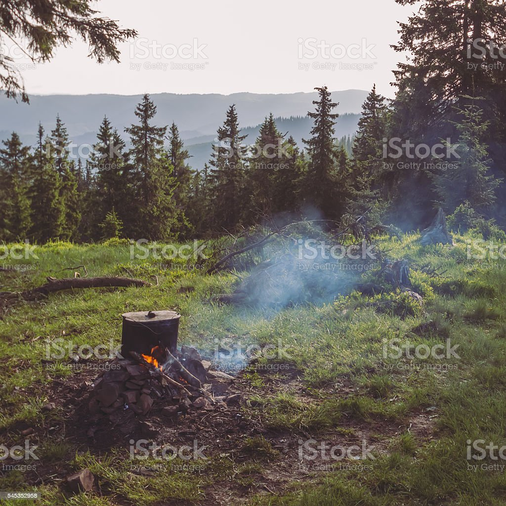 Cooking on campfire during hicking in mountains stock photo