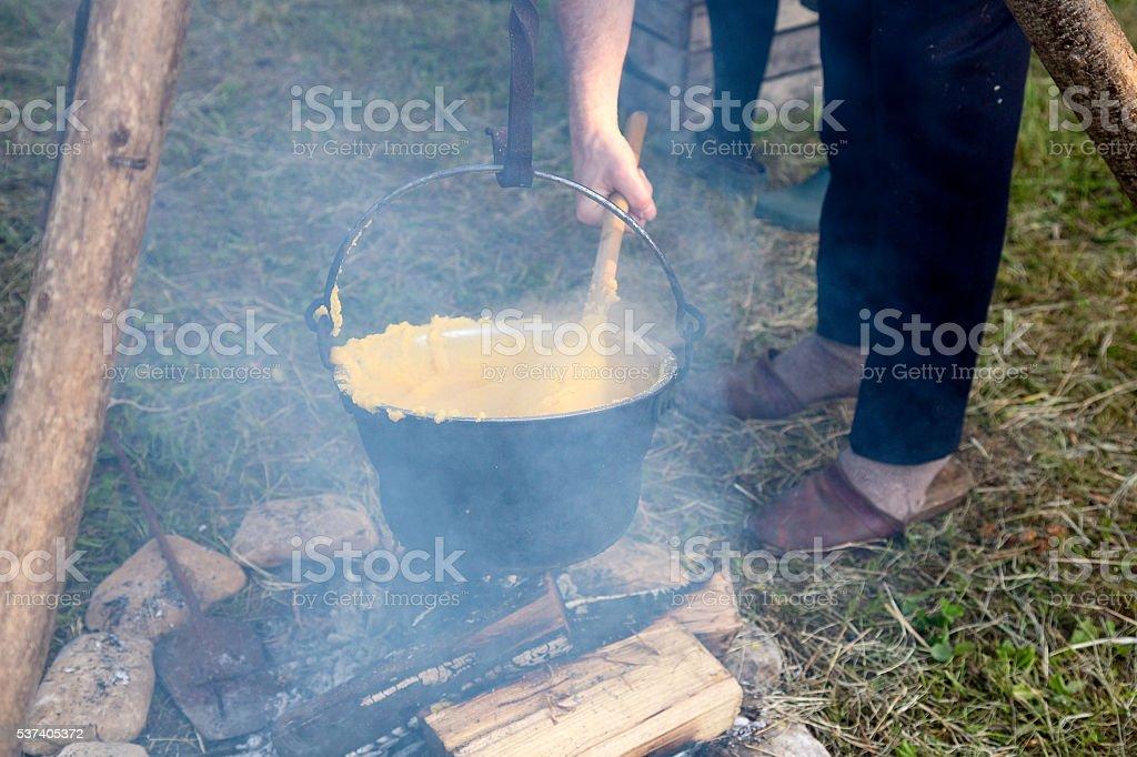 Cooking polenta over campfire in black pot stock photo