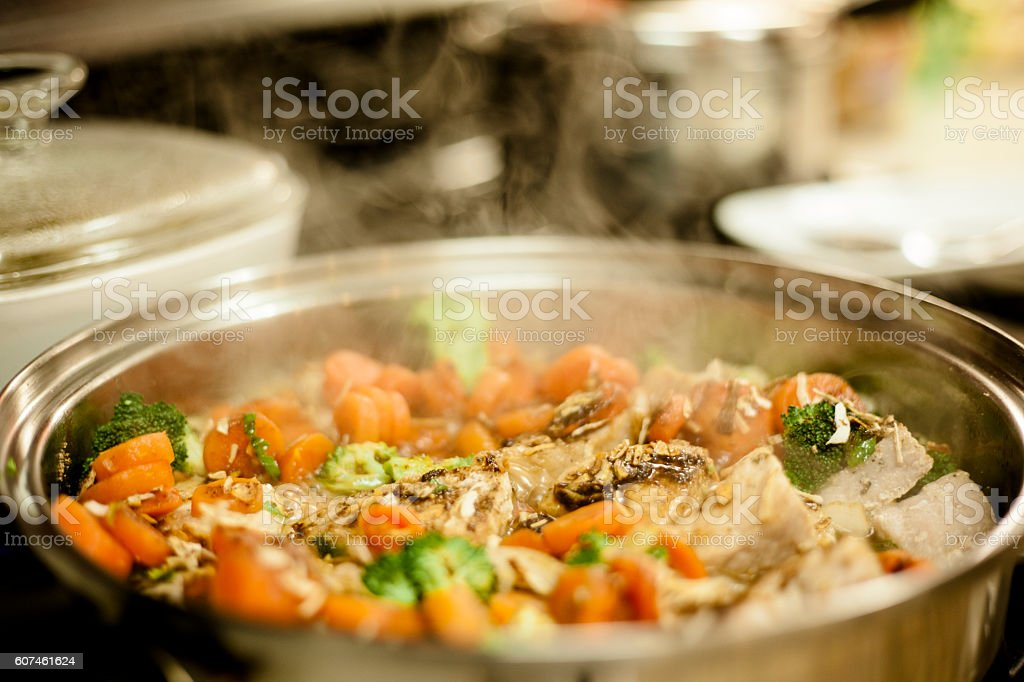 Cooking pot filled with chicken, vegetable soup. stock photo
