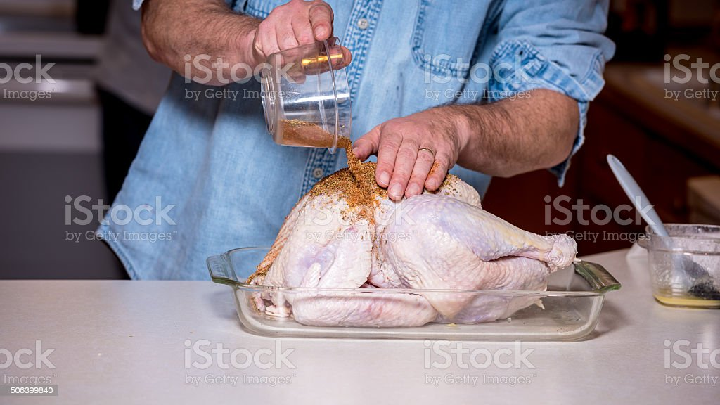 Cooking preperation of a turkey adding a rub stock photo