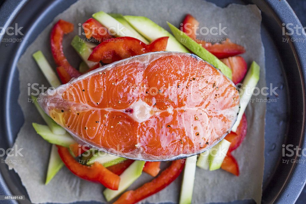Cooking raw steak of red fish salmon on vegetables, zucchini stock photo