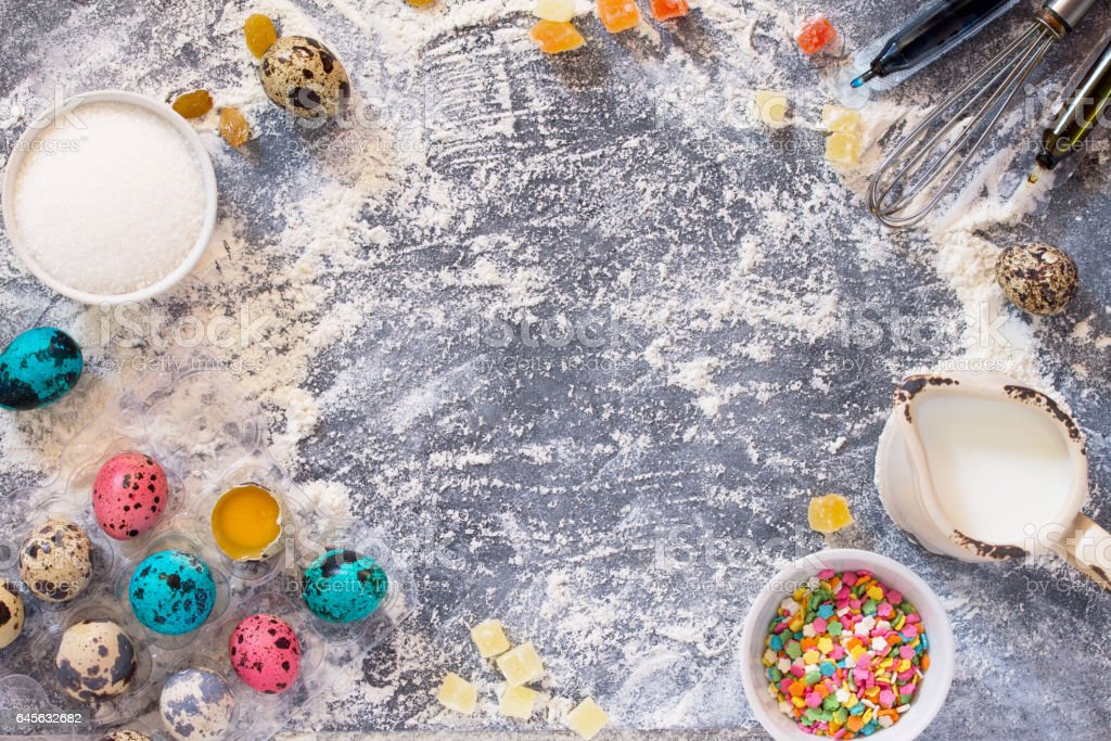 Cooking recipe background for the celebration of Easter: quail eggs, milk, sugar, nuts, candied fruits, and wheat flour on a stone table. Healthy food concept. Food background. stock photo