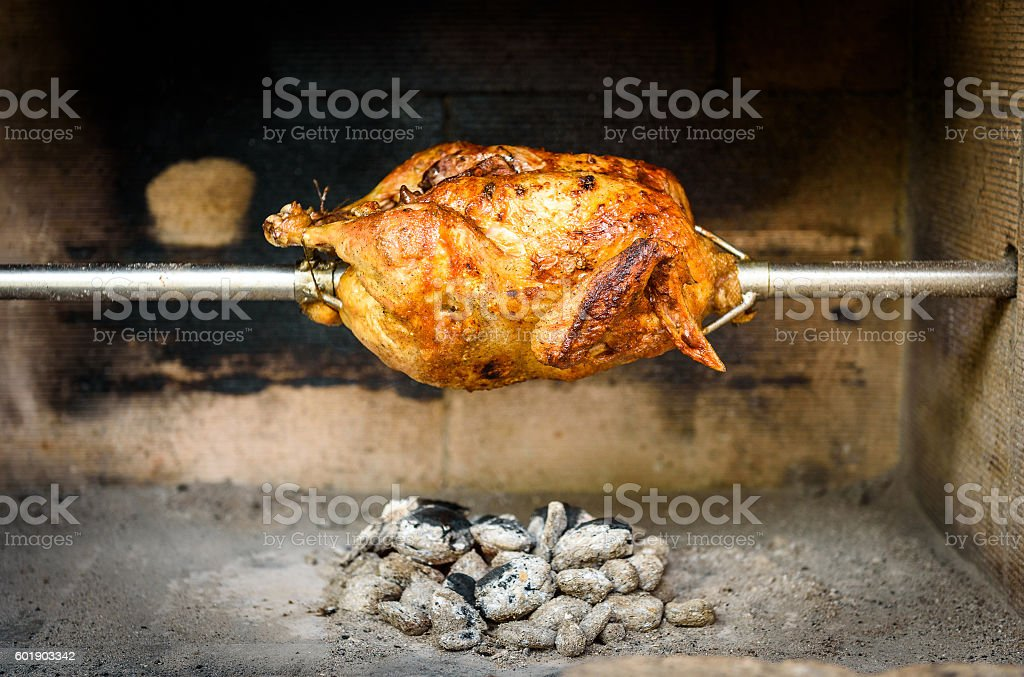 Cooking rotisserie chicken on the grill with Charcoal and Brique stock photo
