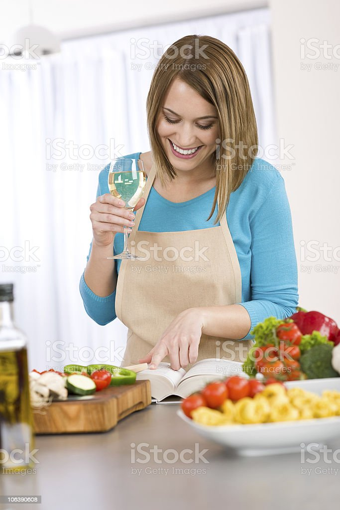 Cooking - Smiling woman reading recipe from cookbook royalty-free stock photo
