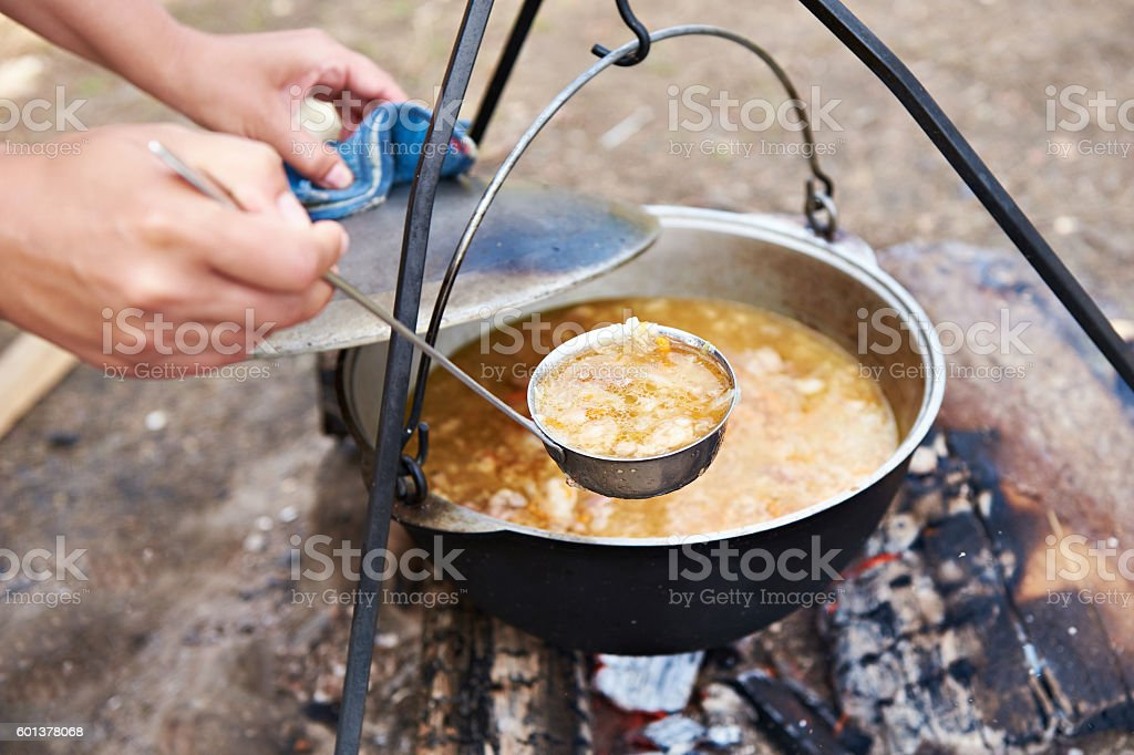 Cooking soup over campfire in hike stock photo