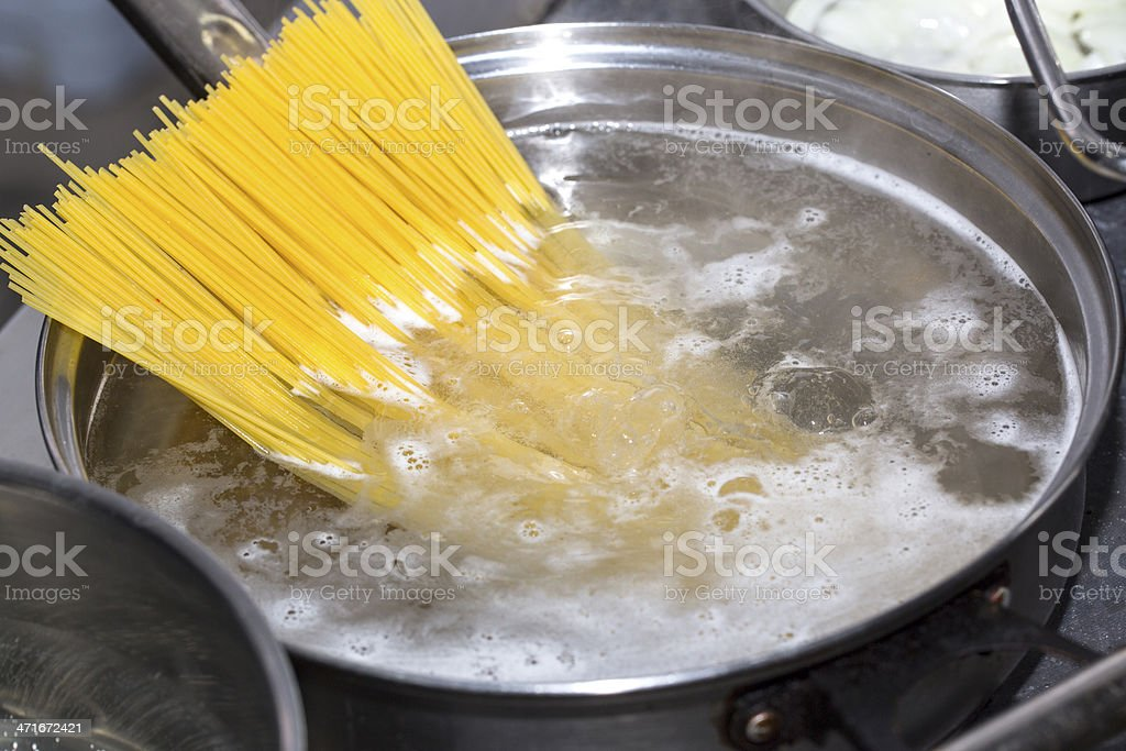 cooking spaghetti in the pan stock photo