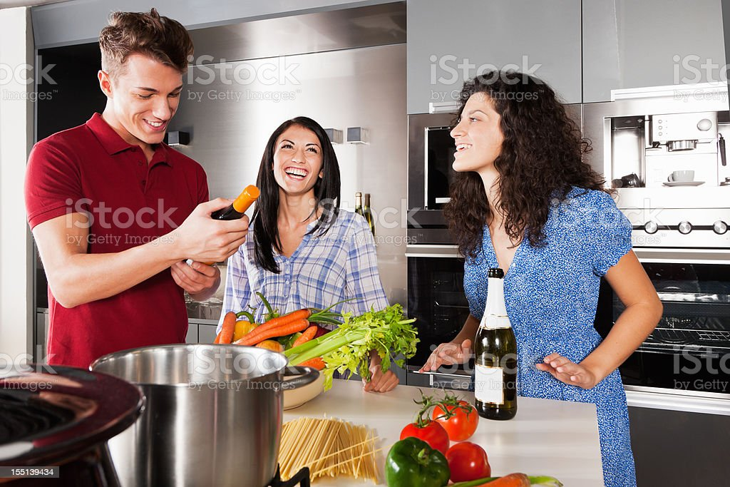 Cooking Together Friends Making Italian Dinner in Modern Kitchen royalty-free stock photo