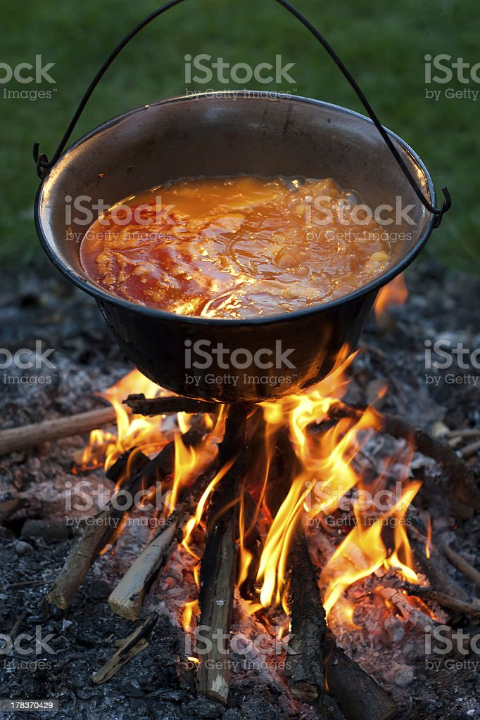 Cooking traditional hungarian paprika potatoes in a cauldron stock photo
