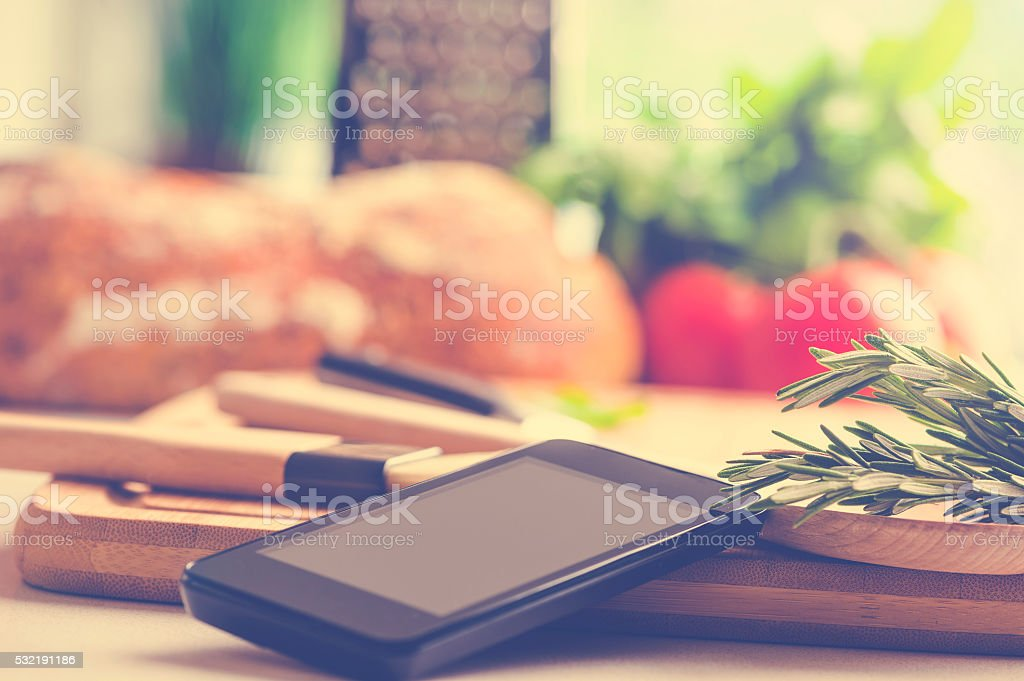 Cooking with a mobile phone in kitchen stock photo
