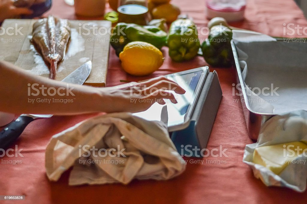 cooking with tablet - checking recipe stock photo