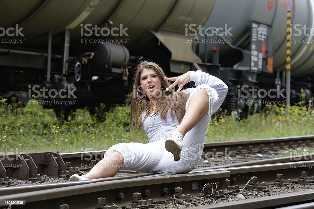 cool, beautiful woman on railroad tracks stock photo