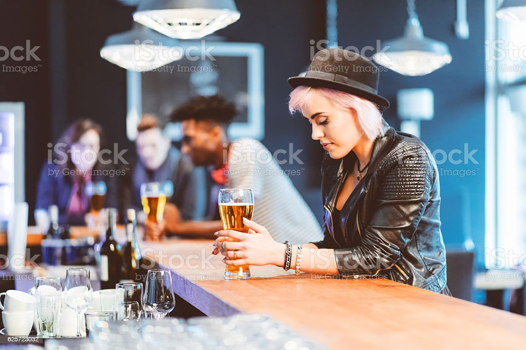 Cool blond young woman drinking beer in a pub stock photo