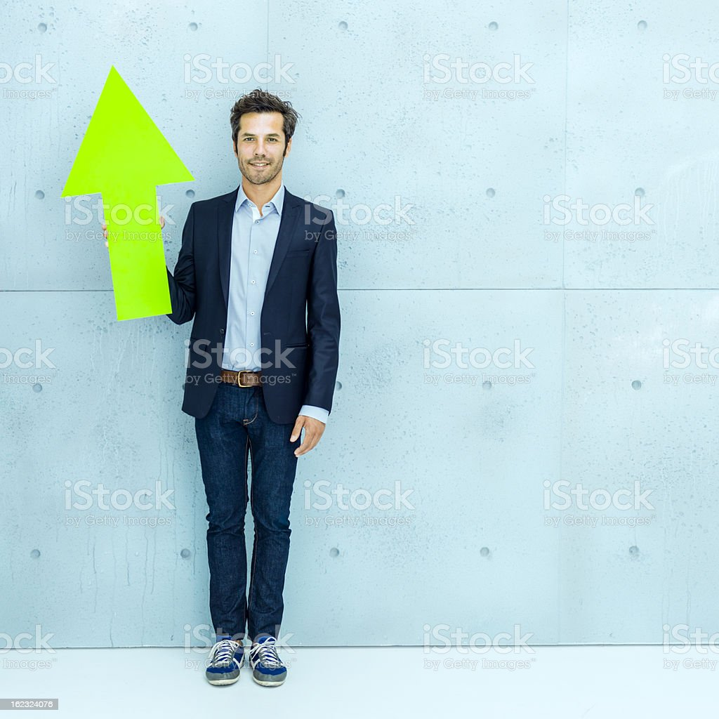 Cool businessman pointing up with green arrow stock photo
