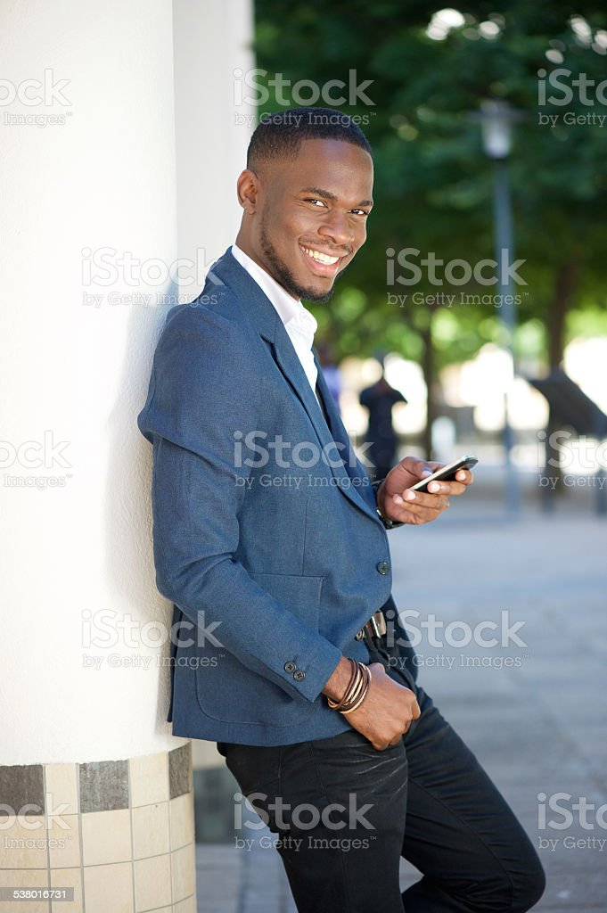 Cool businessman sending text message by mobile phone stock photo