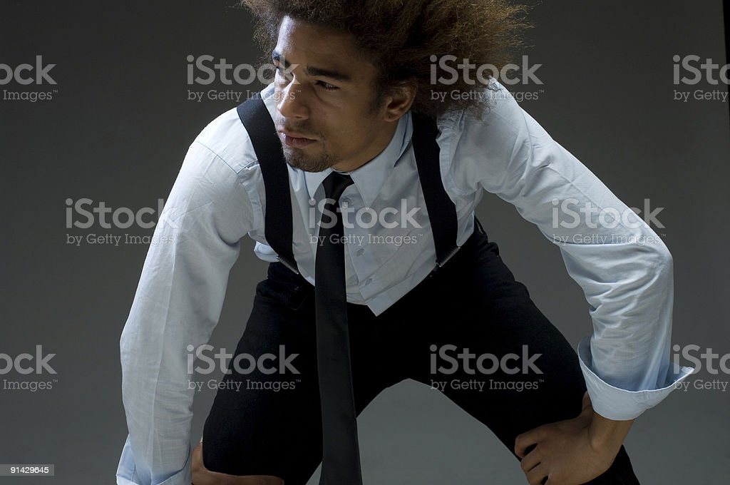 cool businessman with hands on knees stock photo
