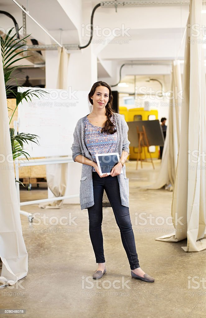 Cool businesswoman holding digital tablet in offic stock photo