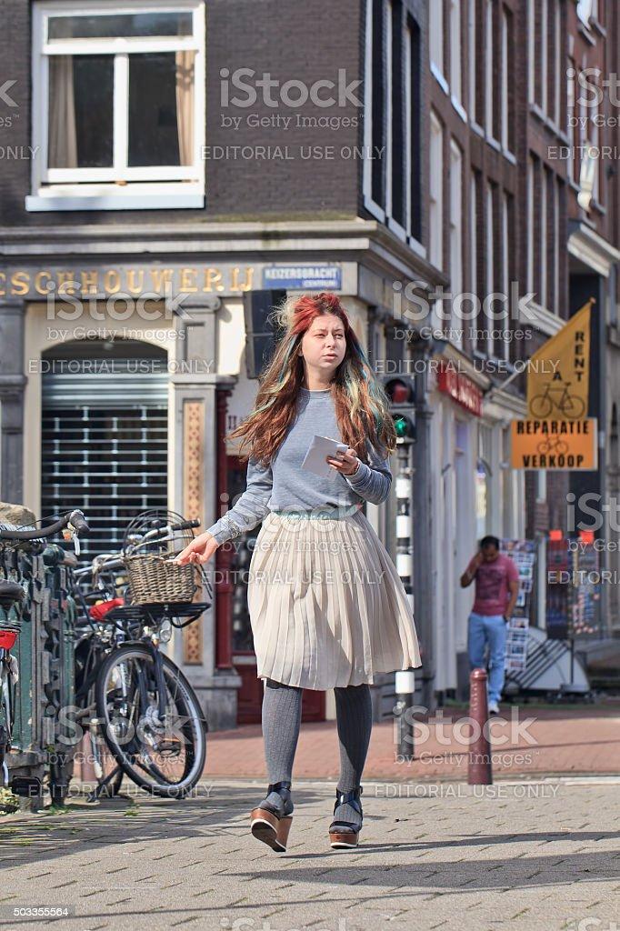 Cool dressed girl walks on a sidewalk in Amsterdam center stock photo