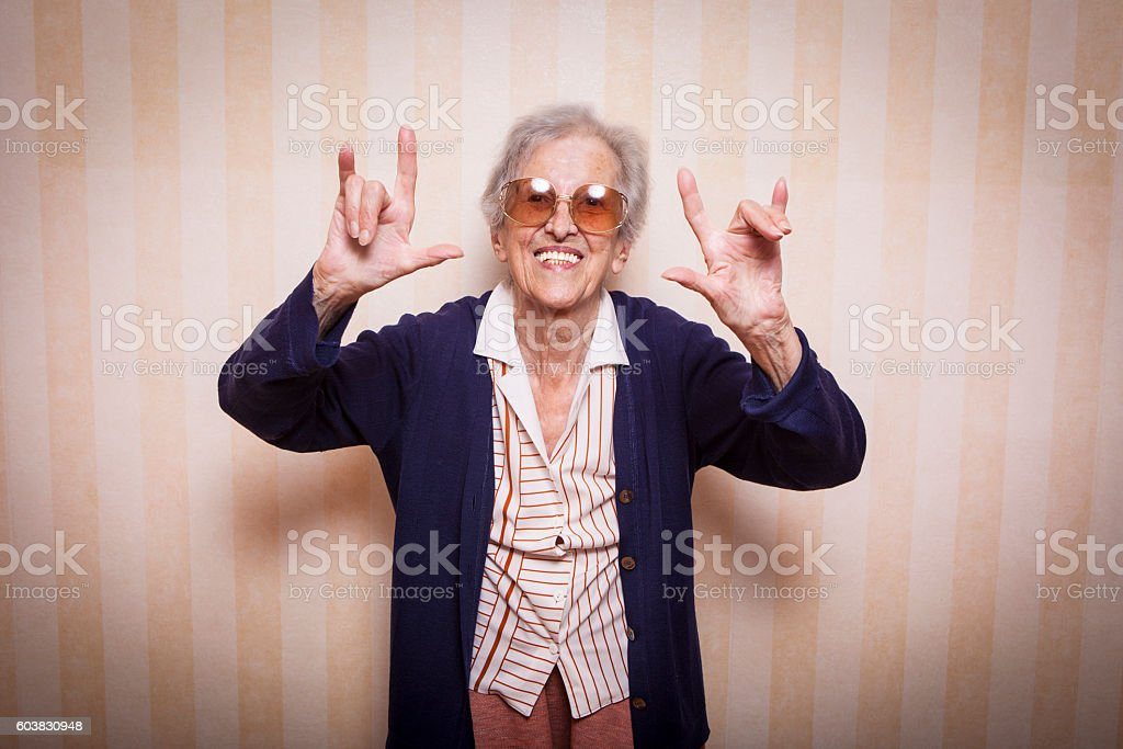 cool elder lady making rock on sign stock photo