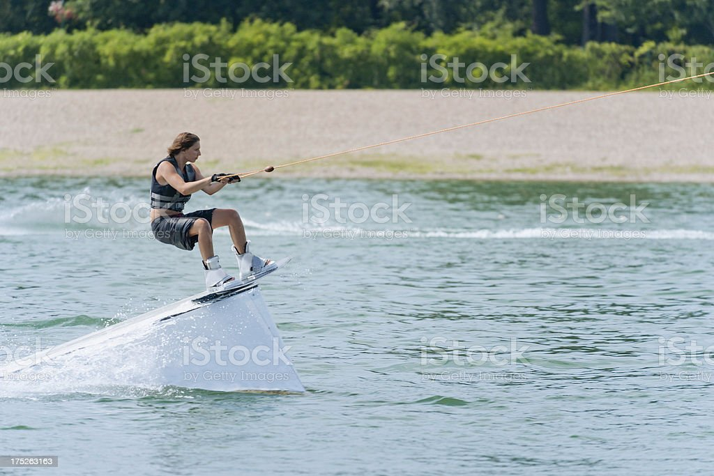Cool girl on wakeboard stunt platform royalty-free stock photo