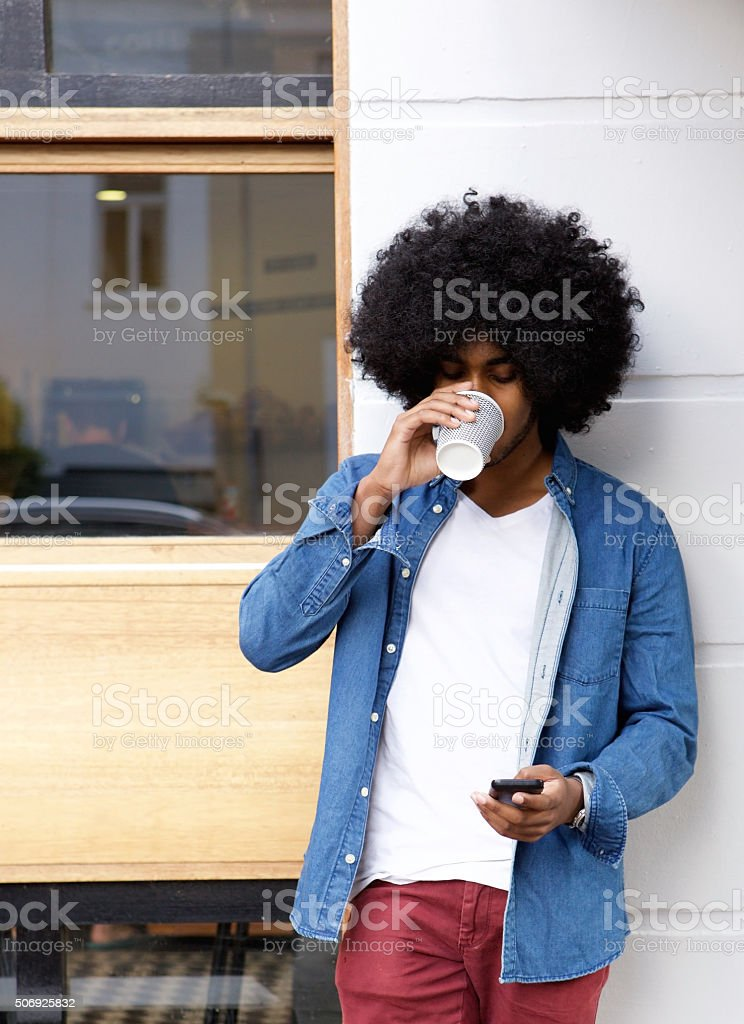 Cool guy drinking coffee and using cellphone stock photo