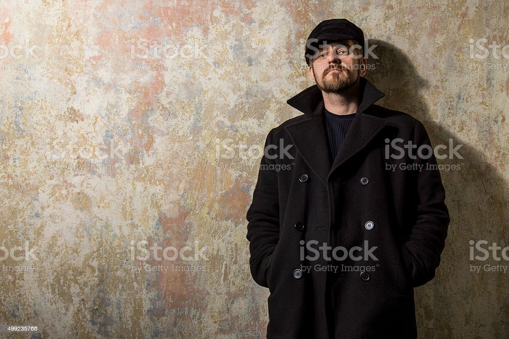 Cool guy rocks coat  and newsboy cap stock photo