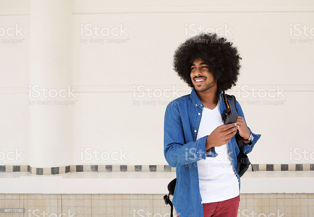 Cool guy smiling with bag and cellphone stock photo