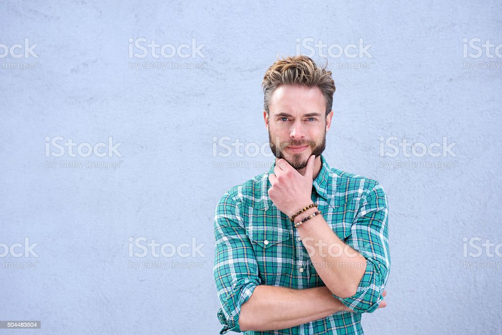 Cool guy smiling with hand on chin stock photo