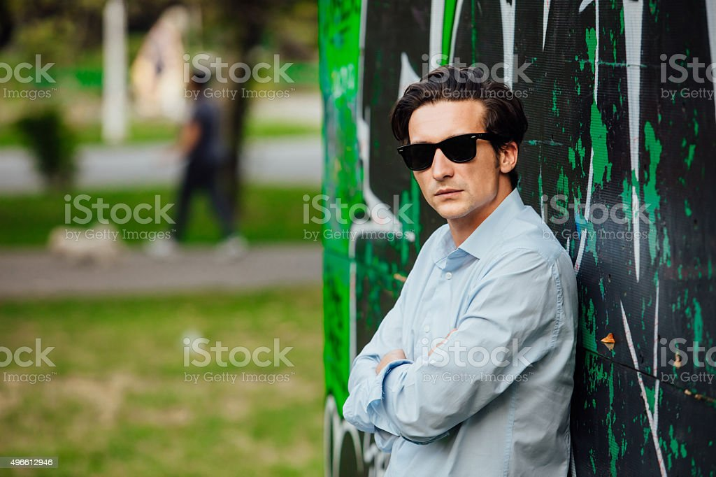 cool handsome man leaning on a wall stock photo