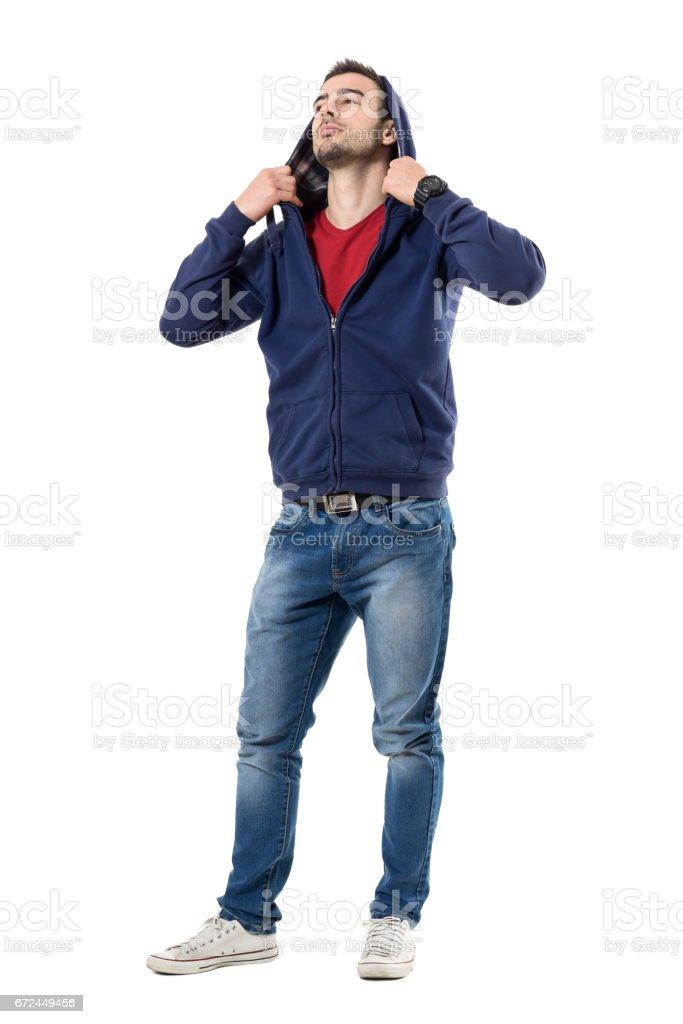 Cool handsome man putting on hoodie of blue sweatshirt looking up stock photo
