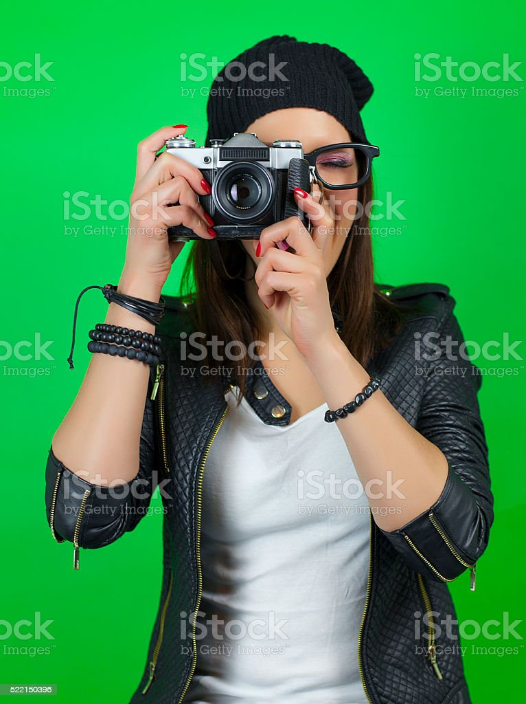 Cool hipster girl taking a picture with old vintage camera stock photo