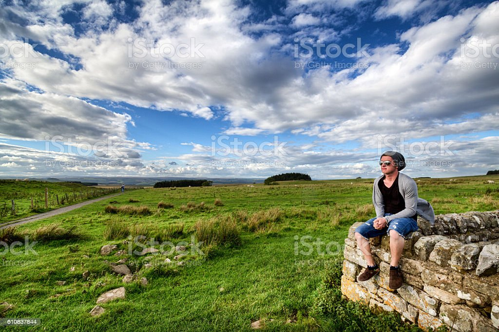 Cool Hipster Traveler Sitting on an Ancient Wall stock photo