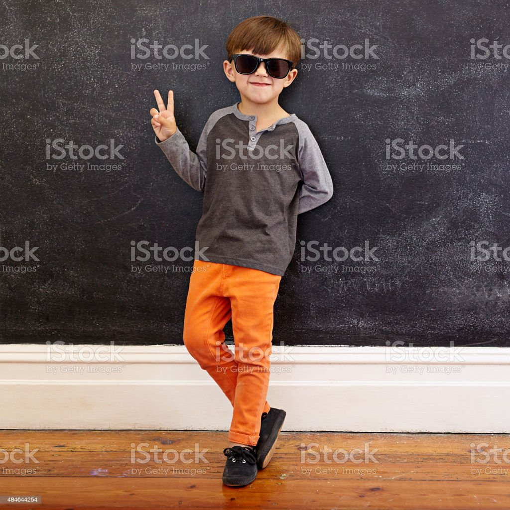 Cool little boy gesturing victory sign stock photo