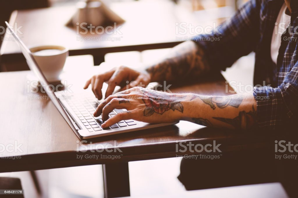 Cool man with tatoos typing on laptop in coffee shop stock photo