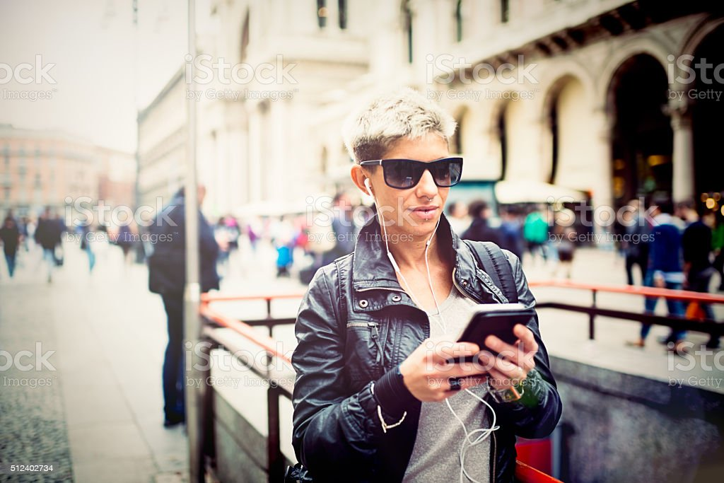 Cool middle age woman listen to music by smart phone stock photo
