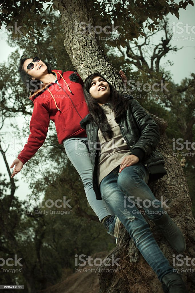 Cool multi ethnic Asian female friends enjoying freedom in nature. stock photo