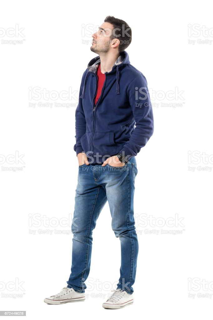 Cool relaxed young casual man in blue sweatshirt looking up interested stock photo