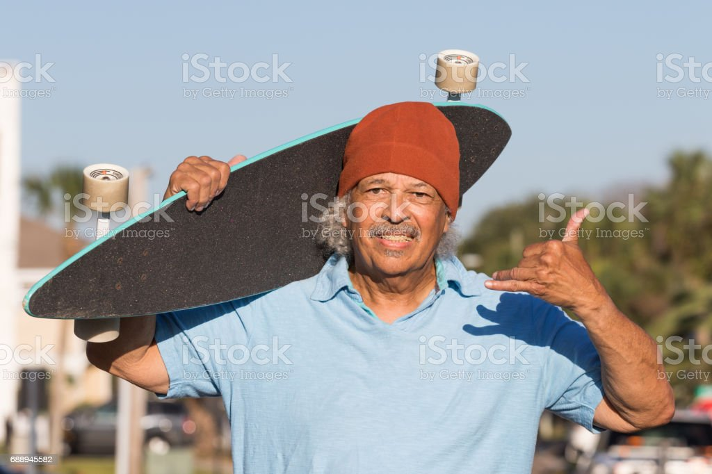 Cool senior hipster posing with a skateboard stock photo