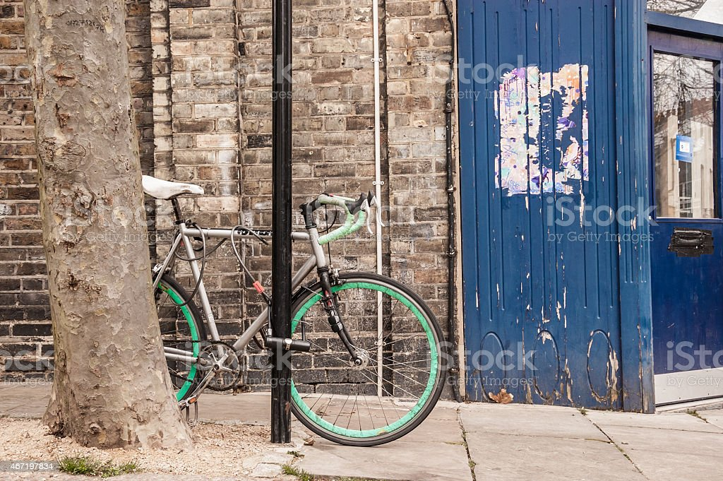 Cool single gear road bicycle locked to a street lamp stock photo